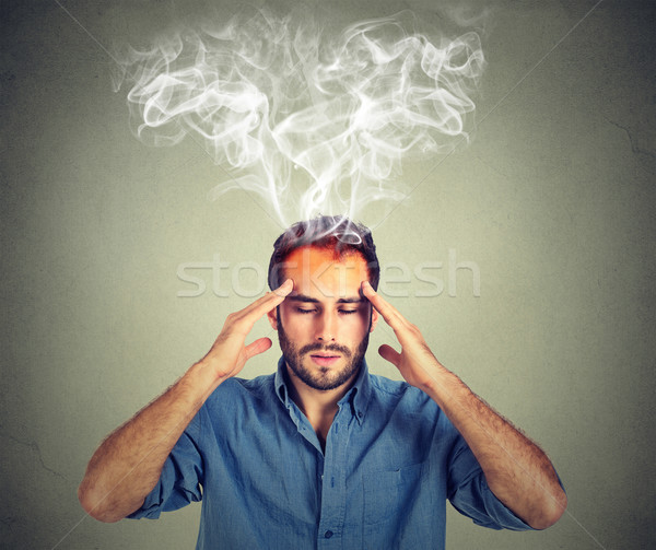 man thinks very intensely having headache isolated on gray wall background  Stock photo © ichiosea