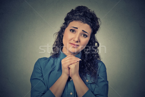 young woman gesturing with clasped hands, please forgive me  Stock photo © ichiosea