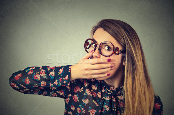 Closeup portrait of scared young woman in glasses covering with hand her mouth Stock photo © ichiosea