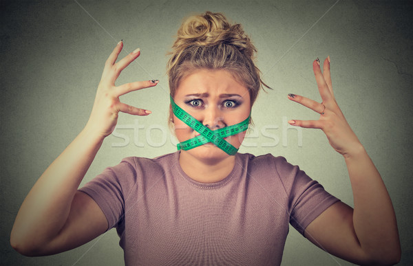 Stock photo: Frustrated woman with measuring tape around her mouth. Diet restriction and stress