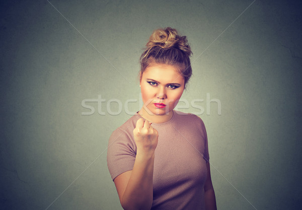 Angry young woman with fist up Stock photo © ichiosea