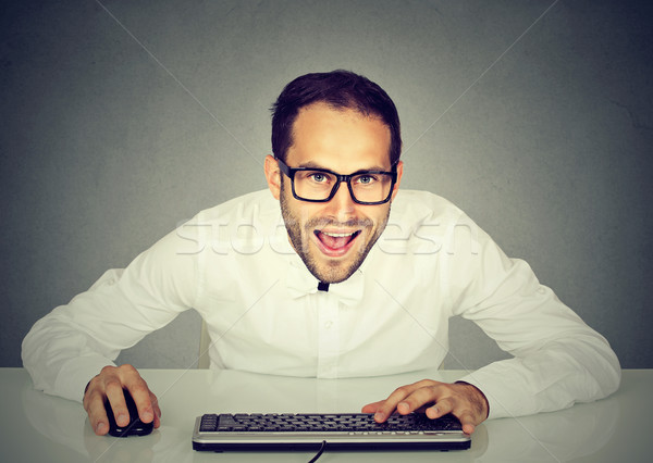 young crazy looking businessman with glasses typing on keyboard Stock photo © ichiosea