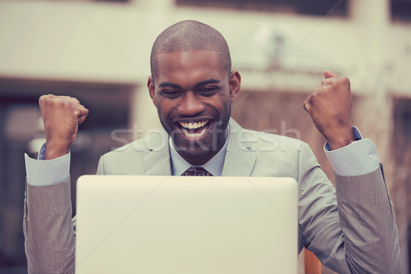 Happy successful man with laptop celebrates success outside corporate office Stock photo © ichiosea