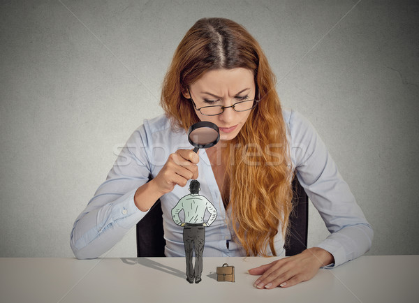 businesswoman skeptically looking at small employee through magnifying glass Stock photo © ichiosea