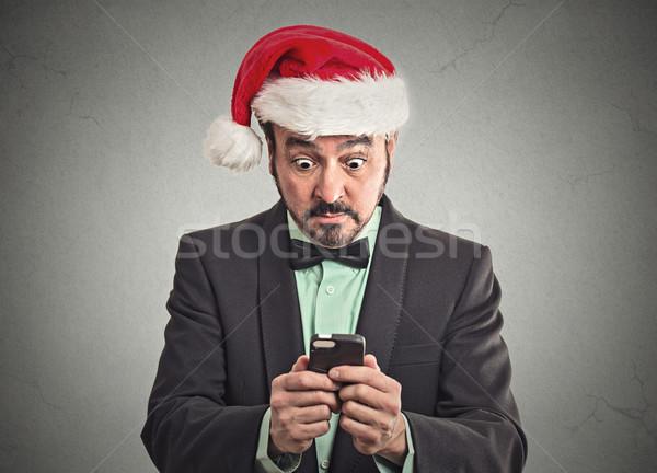 man wearing santa claus hat looking at smartphone shocked  Stock photo © ichiosea