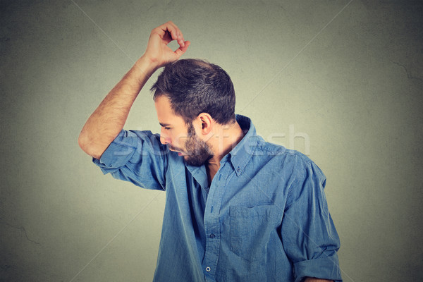 young man, smelling, sniffing his armpit, something stinks Stock photo © ichiosea