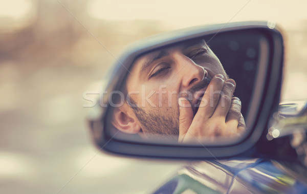 Side mirror view sleepy tired yawning man driving car after long hour drive Stock photo © ichiosea