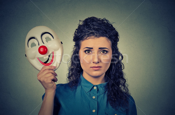 upset worried woman with sad expression holding clown mask expressing cheerfulness Stock photo © ichiosea