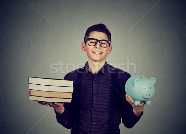 Student loan concept. Man with pile of books and piggy bank  Stock photo © ichiosea