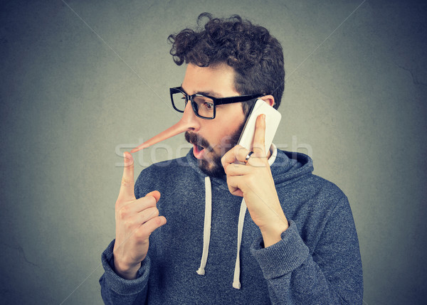 Surprised young man with long nose talking on mobile phone Stock photo © ichiosea