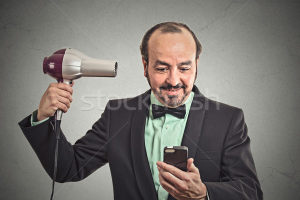 man reading news on smartphone blowing hair with hairdryer Stock photo © ichiosea