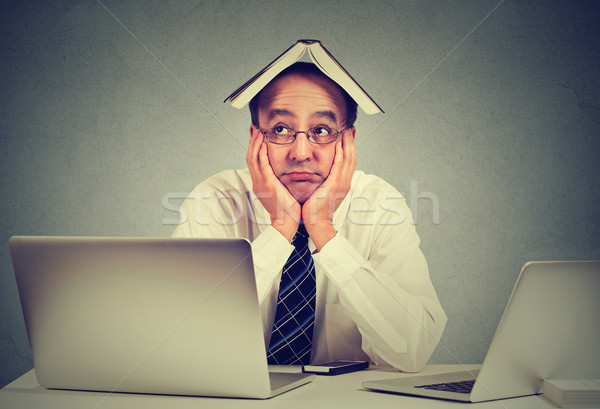 Annoyed, bored, tired, man, funny looking teacher with book on head, sitting at desk, fed up of stud Stock photo © ichiosea