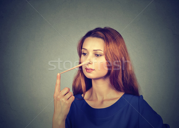 Woman with long nose isolated on grey wall background. Liar concept Stock photo © ichiosea