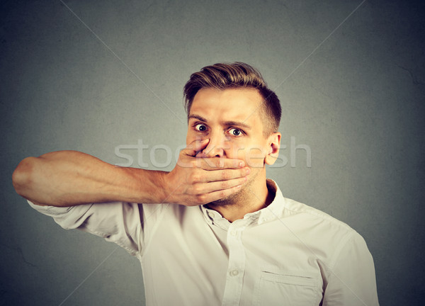 Scared young man covering mouth with hand  Stock photo © ichiosea