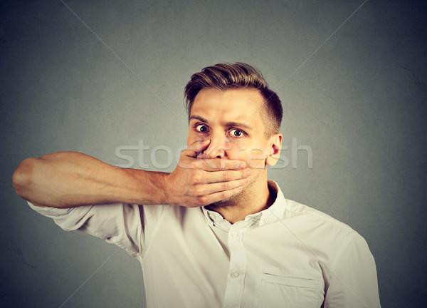 Ijedt fiatalember befogja száját kéz izolált szürke Stock fotó © ichiosea