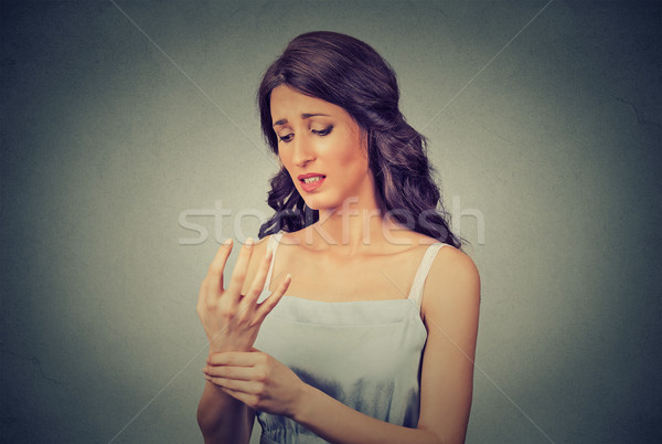 Young woman holding her painful wrist. Negative face expression Stock photo © ichiosea