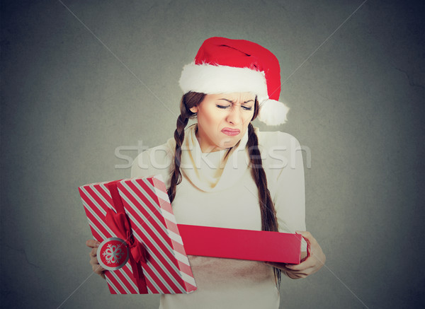woman in santa claus hat opening gift upset  Stock photo © ichiosea