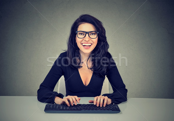 Smiling amazed woman typing on a computer keyboard    Stock photo © ichiosea