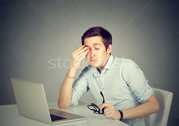 Businessman rubbing his tired eyes after long working hours in office  Stock photo © ichiosea