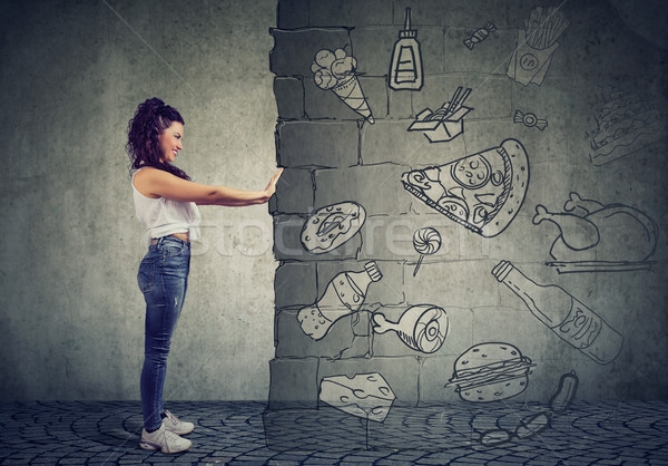 motivated young woman resisting temptation of eating fast foot and choosing better diet.  Stock photo © ichiosea