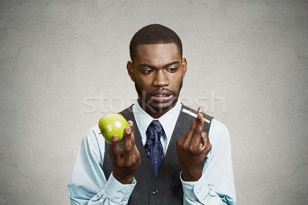 Confused man craving cigarette, making bad health choices Stock photo © ichiosea