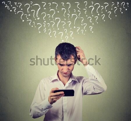 Perplexe jeune homme regarder téléphone Photos Photo stock © ichiosea