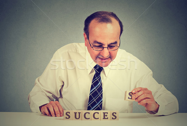 Successful businessman arranging wooden cubes reading success.  Stock photo © ichiosea