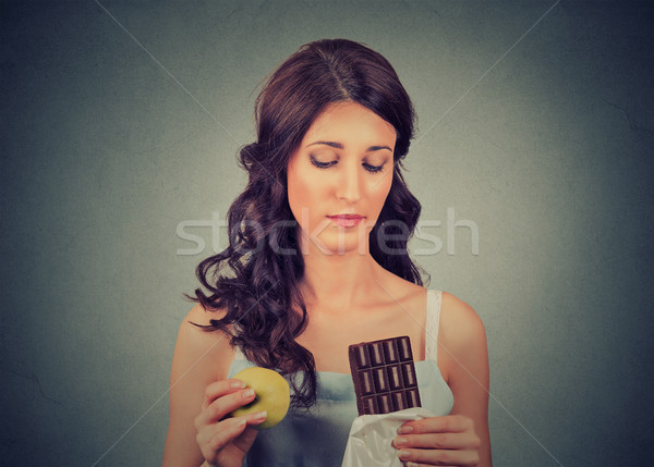 woman with chocolate and apple trying to make a healthy choice control her body weight. Dieting conc Stock photo © ichiosea