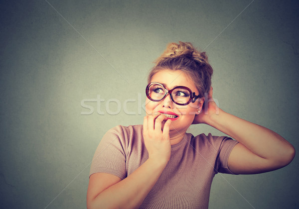 nervous stressed young nerdy woman in glasses biting fingernails looking anxiously Stock photo © ichiosea