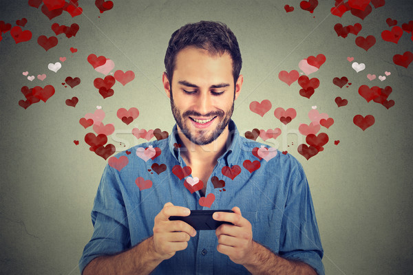 man sending love sms message on mobile phone with hearts flying away Stock photo © ichiosea