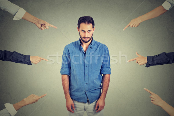 Sad depressed upset man looking down many fingers pointing at him Stock photo © ichiosea
