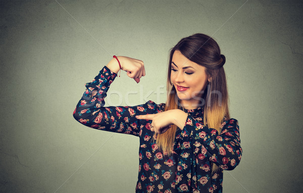 Fit young healthy model woman flexing muscles showing her strength Stock photo © ichiosea