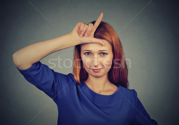 woman giving loser sign on forehead, looking at you Stock photo © ichiosea