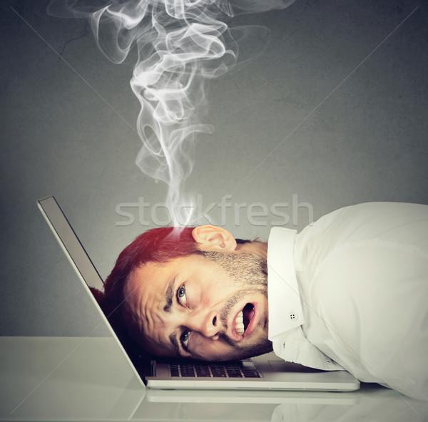 Stressed employee man with overheated brain using laptop  Stock photo © ichiosea