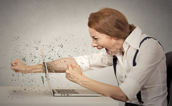 Furious businesswoman throws a punch into computer, screaming Stock photo © ichiosea
