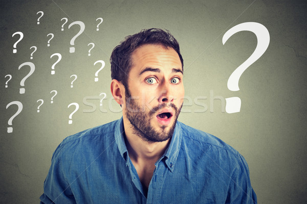 Surprised business man with many question marks  Stock photo © ichiosea