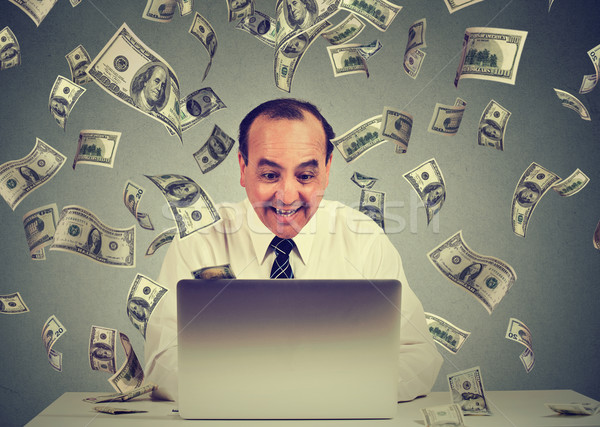Man using laptop building online business making money dollar bills cash falling down. Money rain Stock photo © ichiosea
