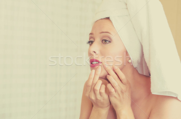 upset woman looking in a mirror frustrated to see zit on her face, pimple Stock photo © ichiosea