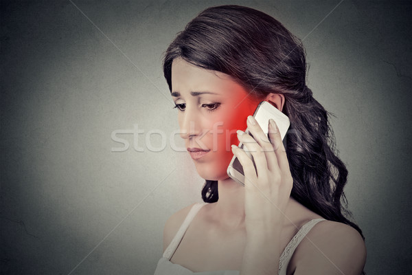 Concerned young woman talking on mobile phone having pain headache  Stock photo © ichiosea