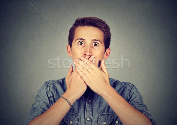 Scared young man covering mouth with hands  Stock photo © ichiosea