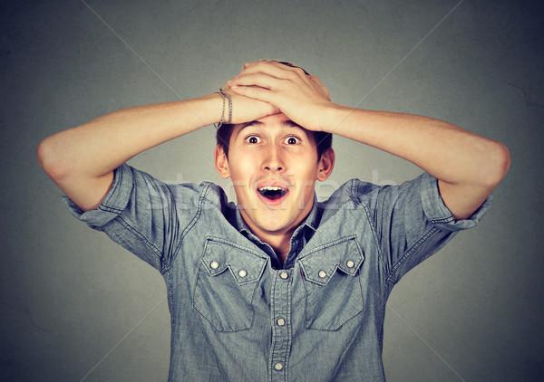 Mosolyog fiatalember meglepődött arc kezek fej Stock fotó © ichiosea