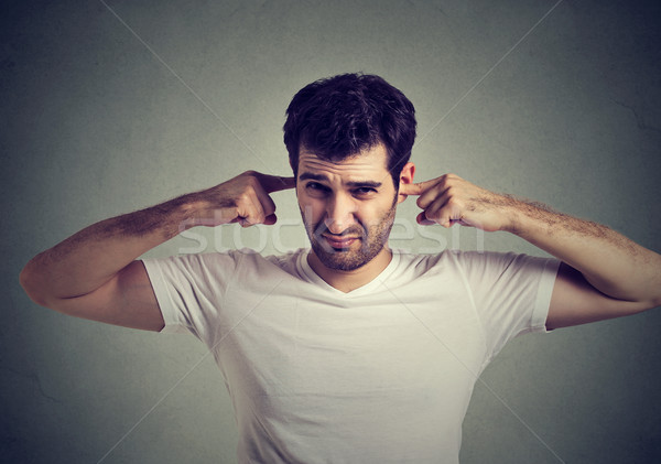 displeased man plugging ears with fingers doesn't want to listen  Stock photo © ichiosea