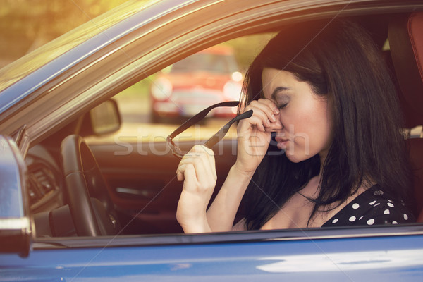 Woman having headache taking off glasses after driving car in traffic jam  Stock photo © ichiosea