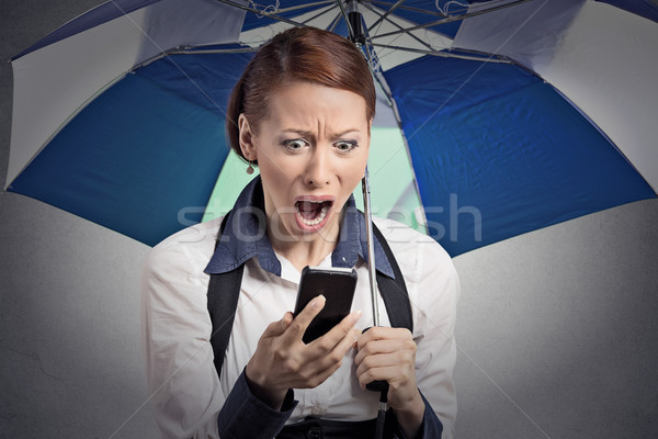 shocked woman reading breaking news on smartphone holding umbrella Stock photo © ichiosea