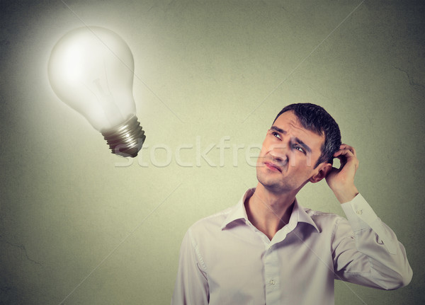 Stock photo: concerned man thinks looking up at light bulb