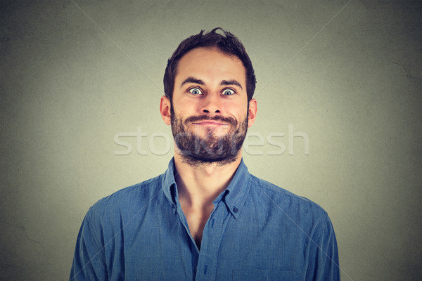 Stock photo: Crazy looking man making funny faces isolated on gray wall background