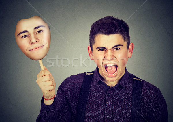 Angry man taking off mask with calm face expression  Stock photo © ichiosea