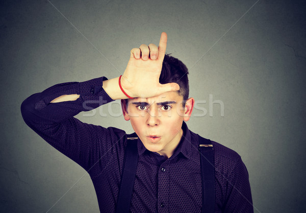 Angry man showing loser sign looking with disgust at camera  Stock photo © ichiosea