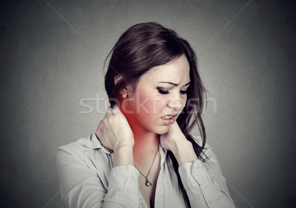 Spine disease. Woman massaging painful neck colored in red  Stock photo © ichiosea