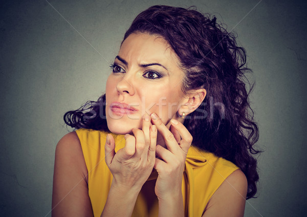 woman looking in mirror squeezing acne or blackhead on face Stock photo © ichiosea